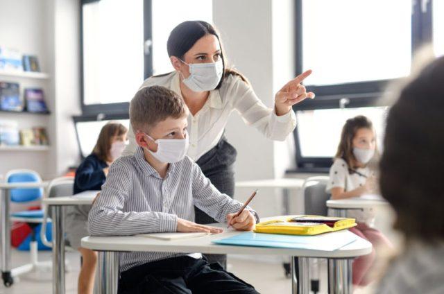 Maestra e alunno con mascherina